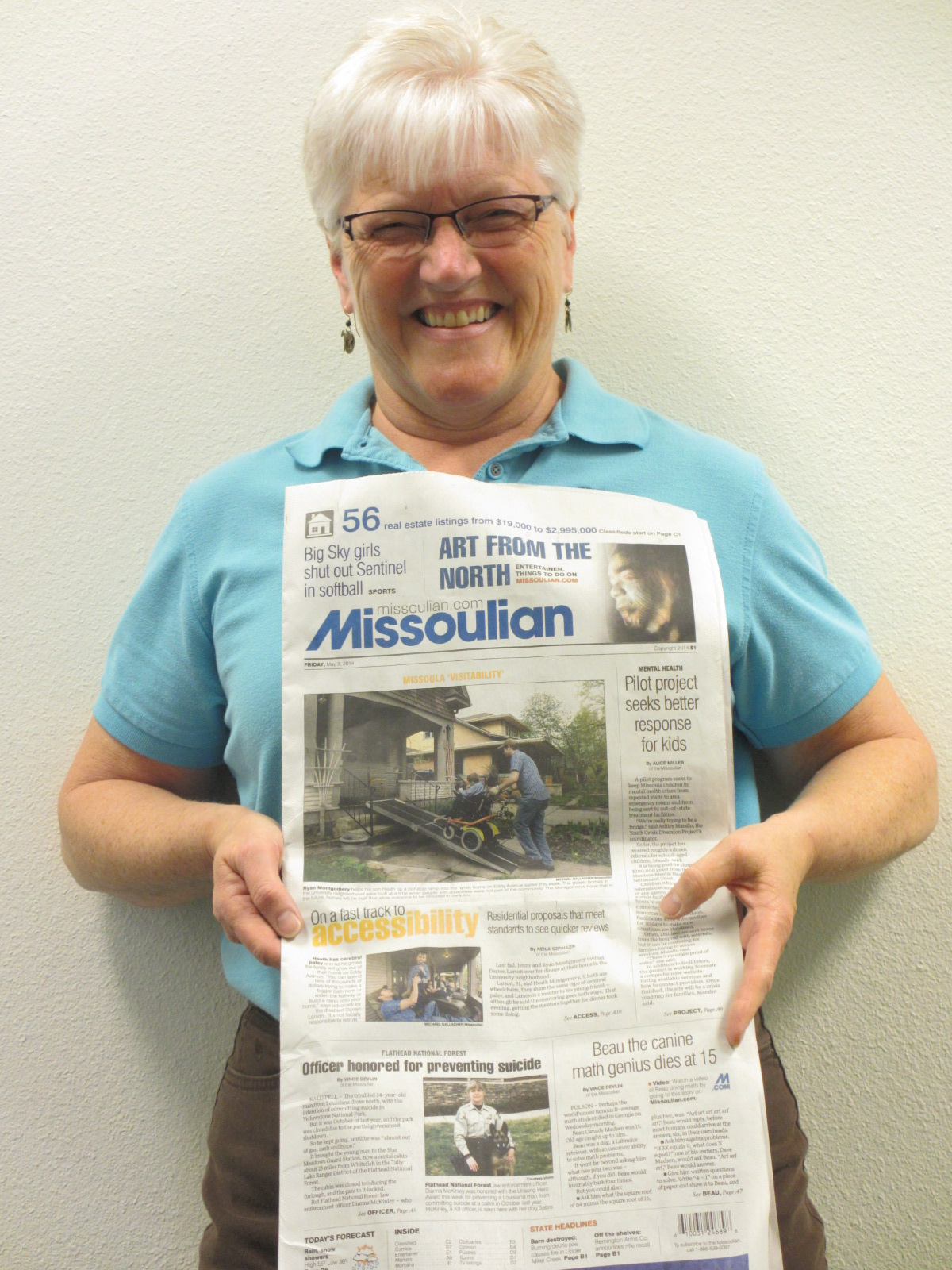 Summit's Jude Monson holding up a Missoulian newspaper showing a story about Visitability on the front page