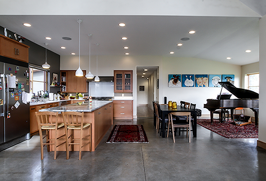 A very open kitchen and dining room with a grey, possibly stone, floor. A kitchen island, stainless steel refridgerator, black dining table, piano, and several decorative rugs are visible.