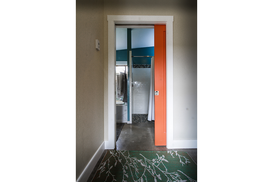 A green rug gives way to an orange pocket door, sliding into a wall. The entrance leads to a bathroom, which has a shower that is seemlessly accessible from bathroom floor with no threshold.