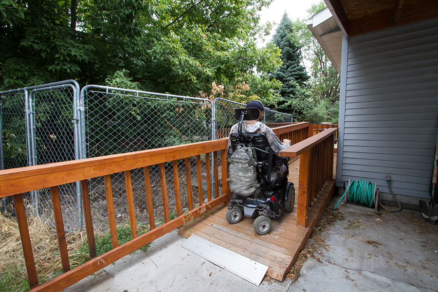 A man wearing a baseball cap uses a power wheelchair to travel up the back wooden ramp toward his rear deck.