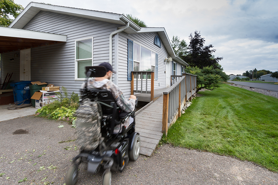 A man wearing a baseball cap uses a power wheelchair to travel up the front grey ramp toward his front door. A camo-colored bag hangs from the back of the chair.