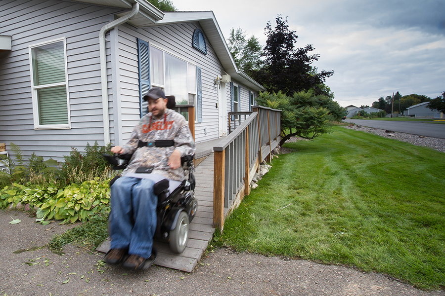 The man drives his power wheelchair off the end of the grey ramp onto the driveway. Towards the street is a green lawn with several manicured bushes near the home.