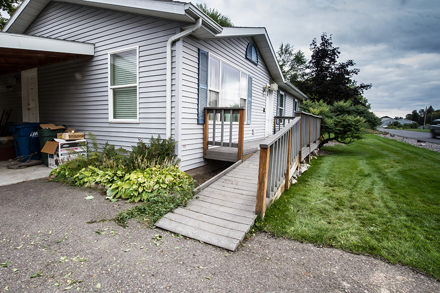 The grey ramp in the front of the house hangs nearly a foot into the drive. Several light green bushes press against the side with a safety guard to prevent wheels from sliding off. On the street-facing side, there is a handrail that ends just before the driveway.