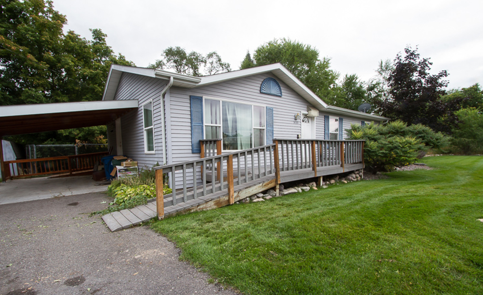 A grey, modular home features two long ramps connecting the front and back decks to a driveway.  The front deck is made out of grey composite boards, while the rear deck and ramp are made from brown stained wood boards.